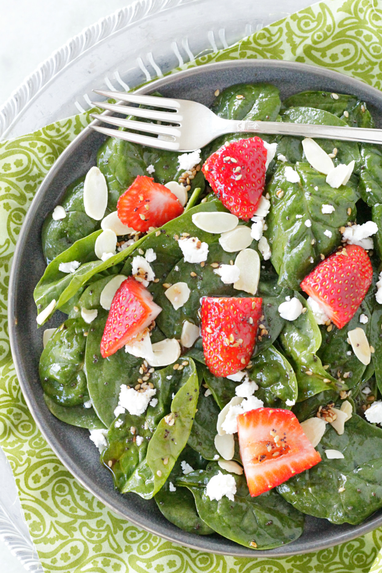 top view of spinach strawberry salad on gray plate with fork on top