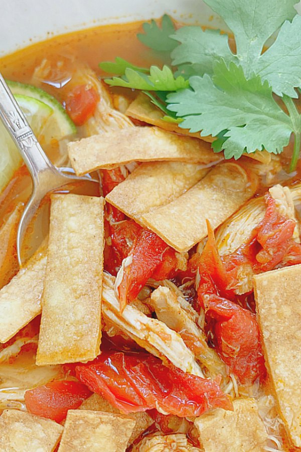 spoon dipping into chicken tortilla soup topped with tortilla strips