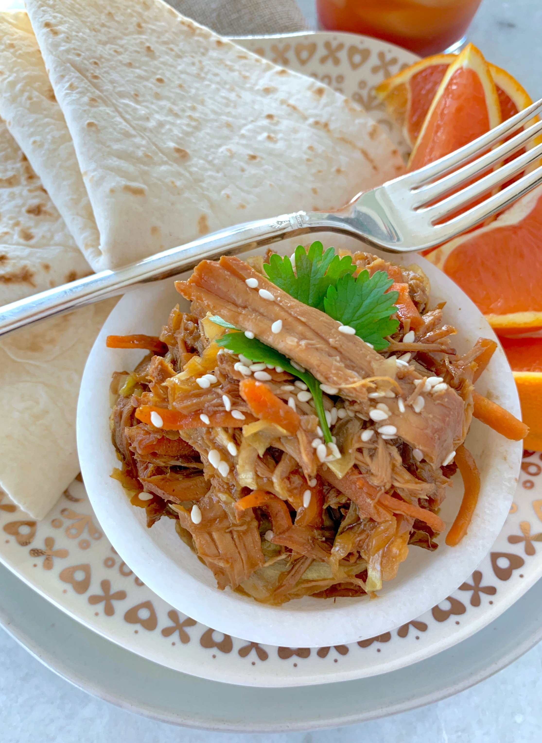 slow cooker moo shu pork on plate with tortillas and orange slices