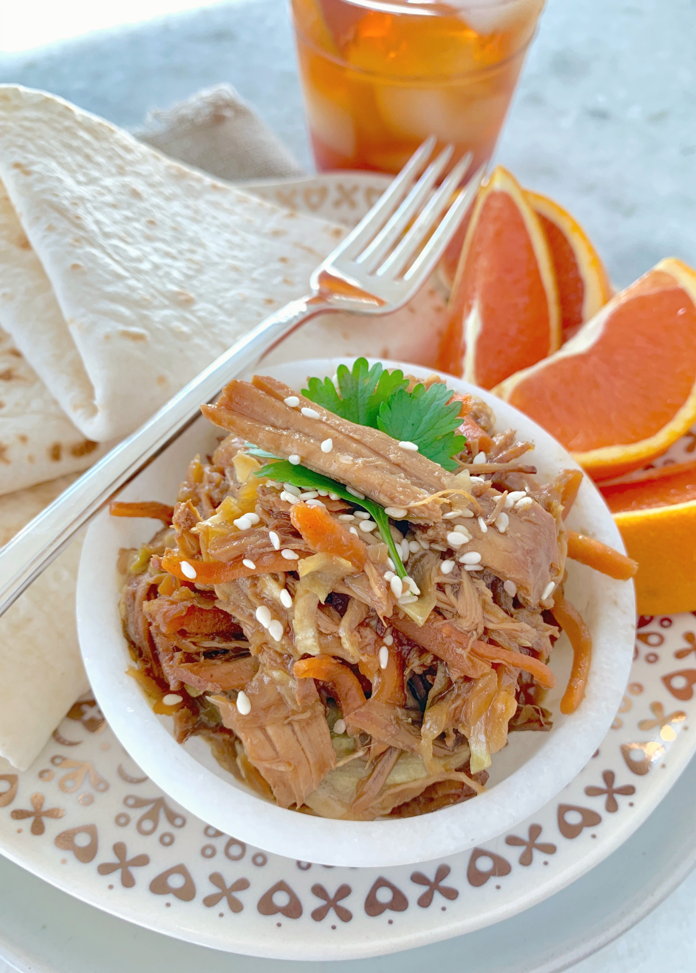 slow cooker moo shu pork on a plate with tortillas and orange slices