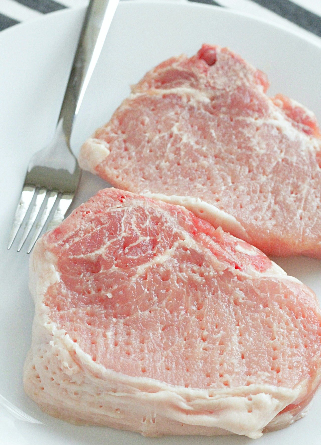 raw pork chops on a plate