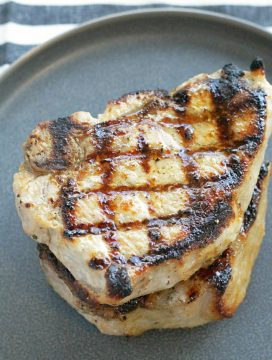 perfectly grilled pork chops stacked on a plate
