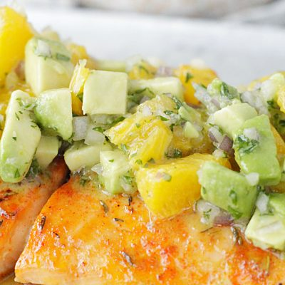 close up view of citrus salmon with avocado and orange salsa on top