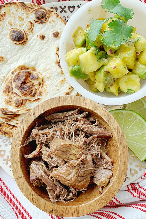 tortillas, pineapple salsa and short rib meat on a plate