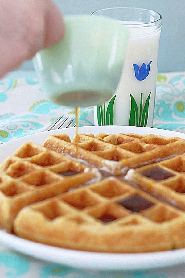syrup being poured over whole grain belgian waffle