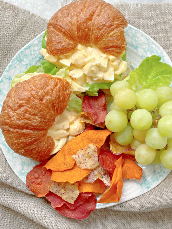 deviled egg salad sandwiches on a plate with chips and grapes