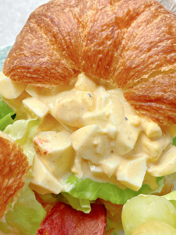 close up view of deviled egg salad on a croissant