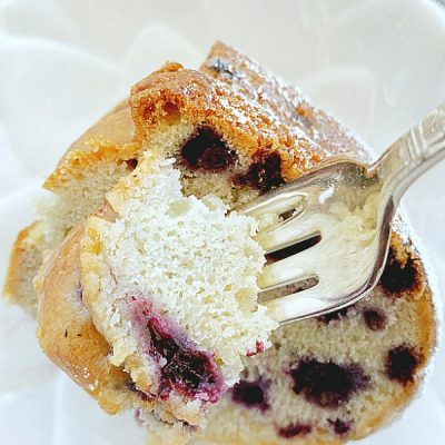 taking a bite out of a slice of blueberry bundt cake