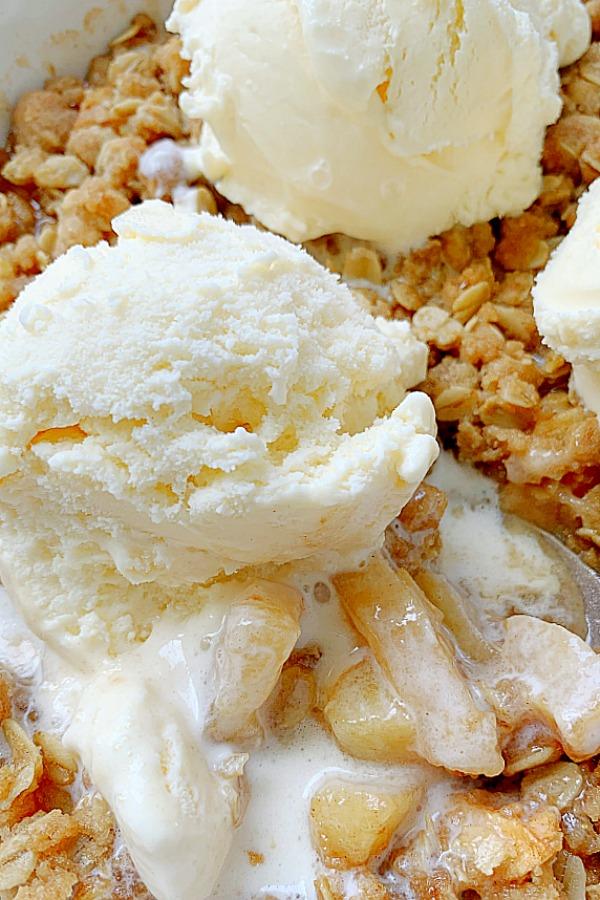 close up of a scoop of vanilla ice cream melting into apple crisp
