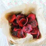 fried beet chips overhead view in basket with parchment paper