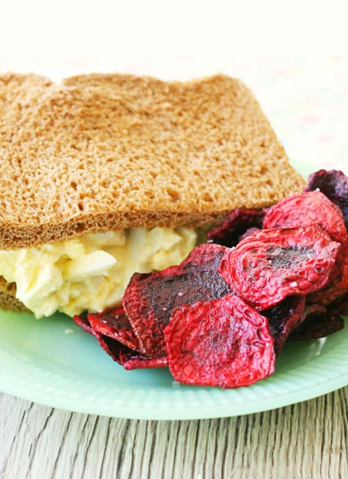 fried beet chips on plate with egg salad sandwich