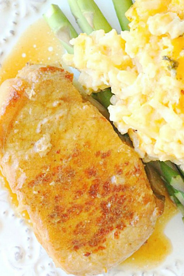 slow cooker pork chops on plate with cheesy potatoes