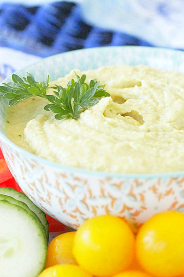 side view of tahini free hummus in bowl topped with fresh parsley