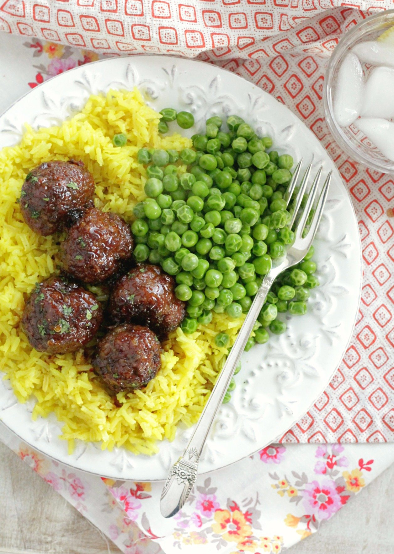 lemon rice on a plate with meatballs and peas