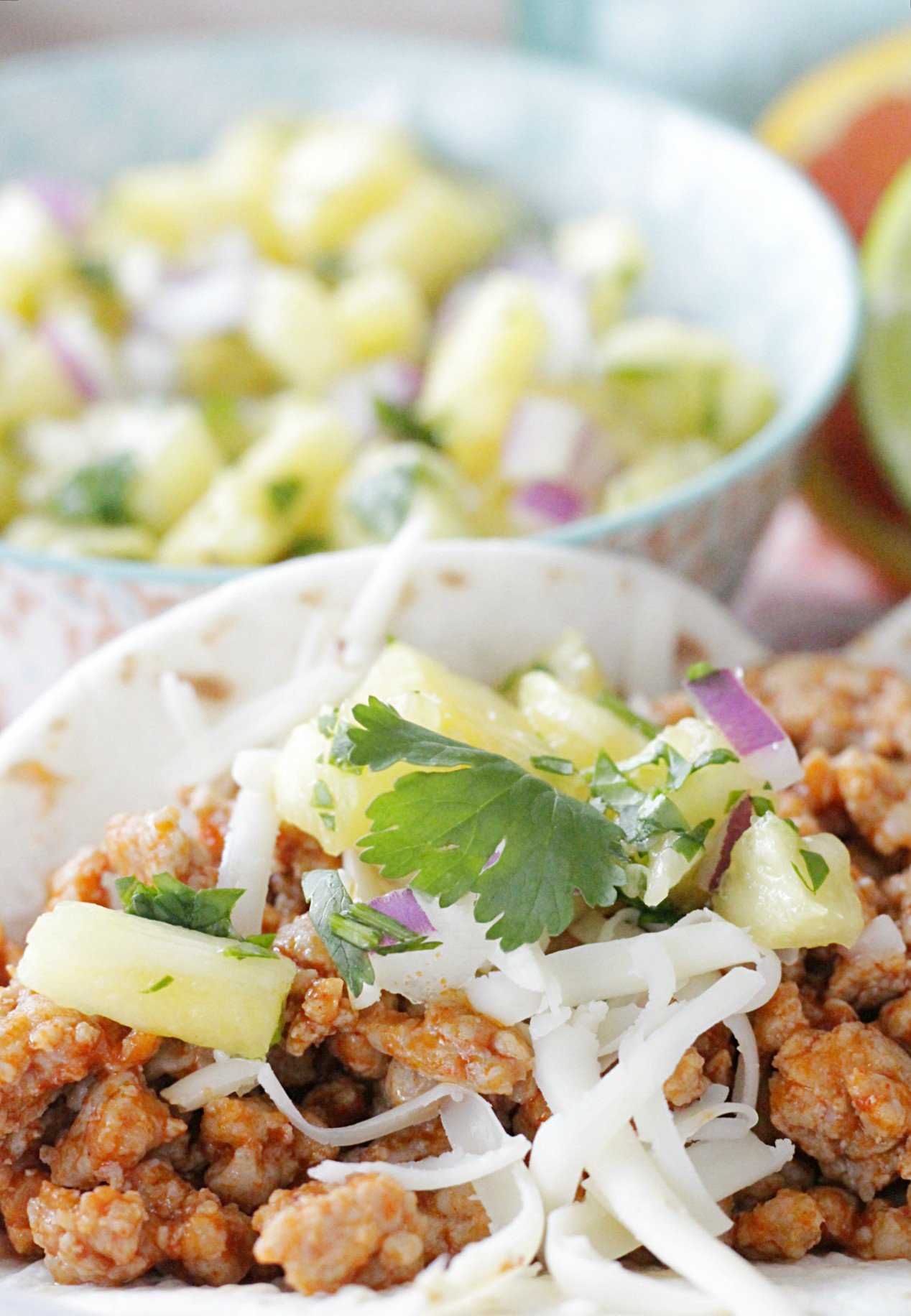 pork tacos with bowl of pineapple salsa