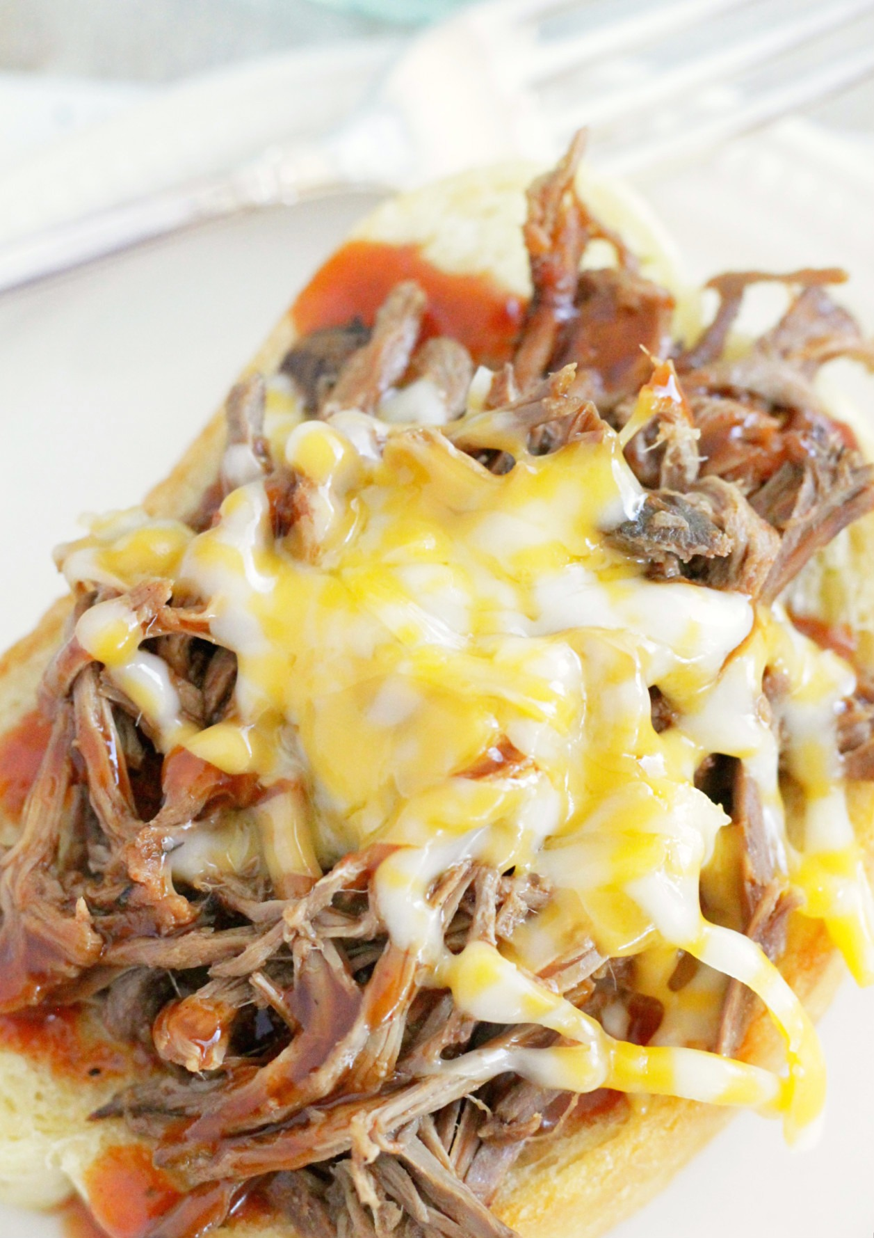 cook once eat all week with shredded beef top view of pile of bbq beef topped with melted colby jack cheese