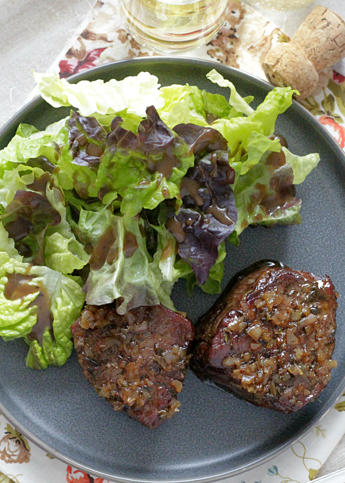 reverse sear filet mignon with champagne butter sauce overhead view with salad and champagne