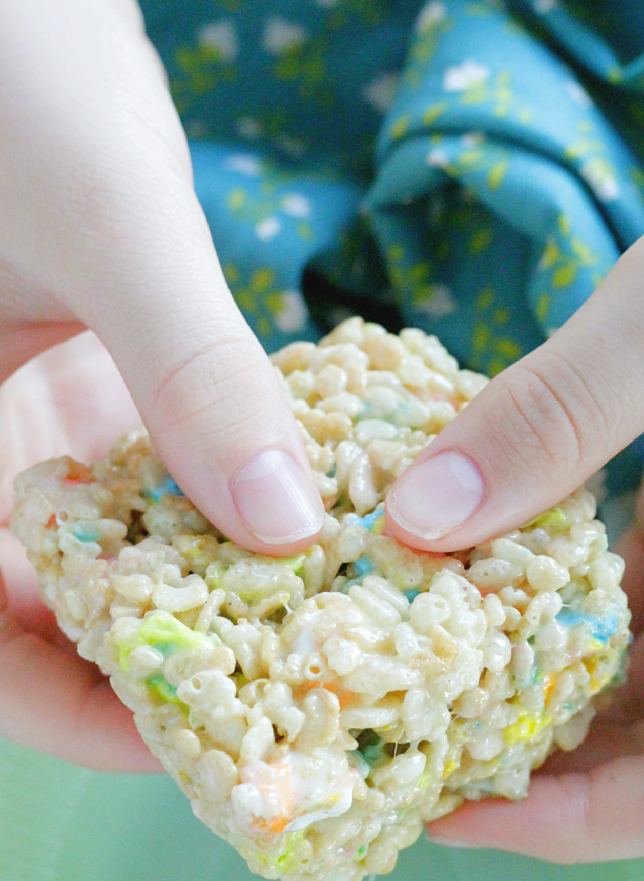 st. patrick's day krispie treat square being held in boy's hands