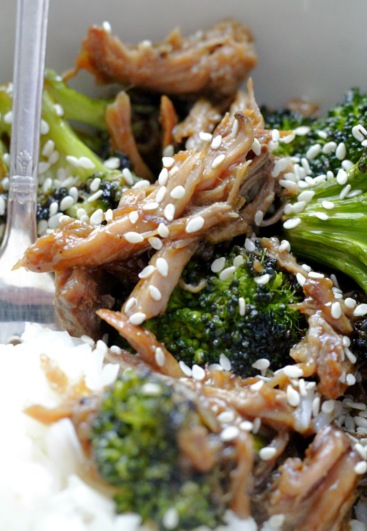 close up of pork teriyaki bowl in off-white bowl with fork