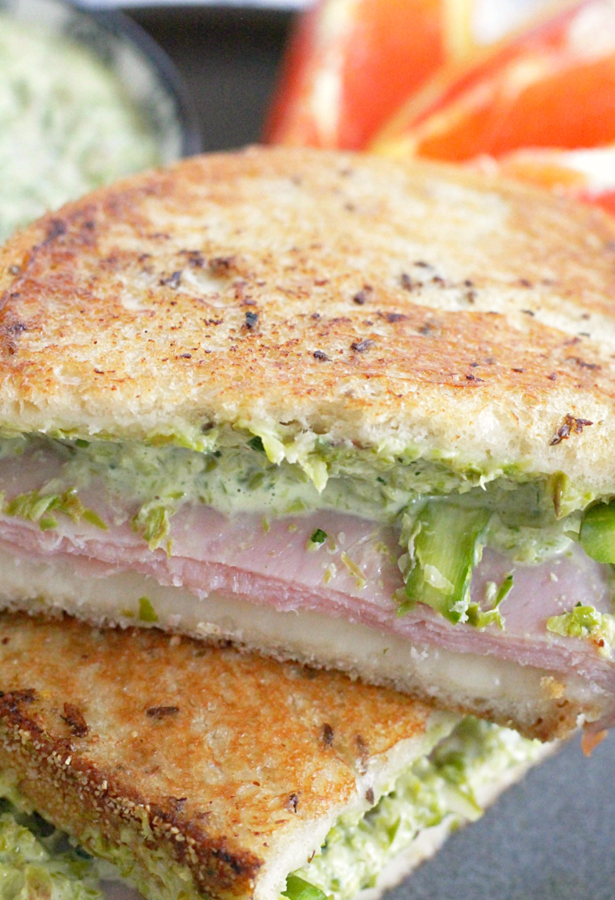 close up of grilled ham and cheese sandwich with asparagus sliced in half