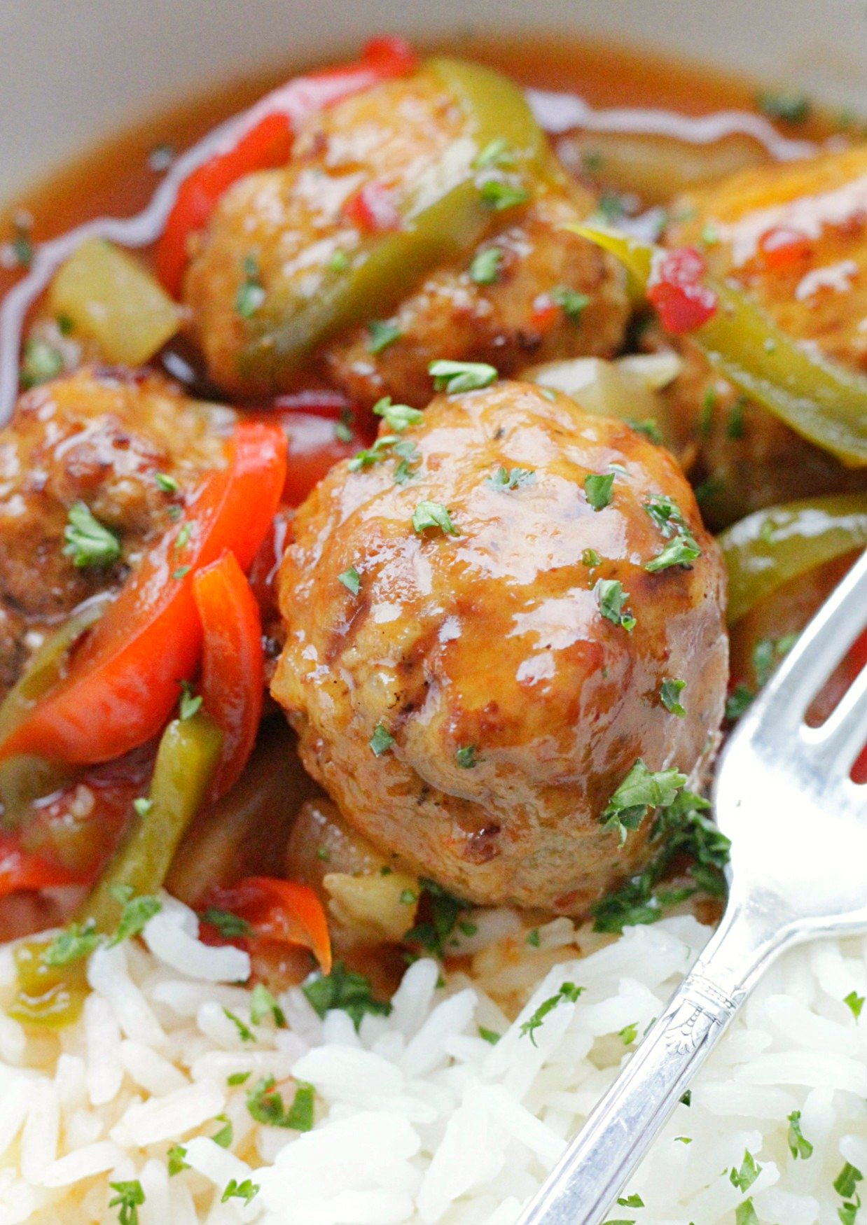 close up view of slow cooker sweet and sour meatballs in a bowl with white rice