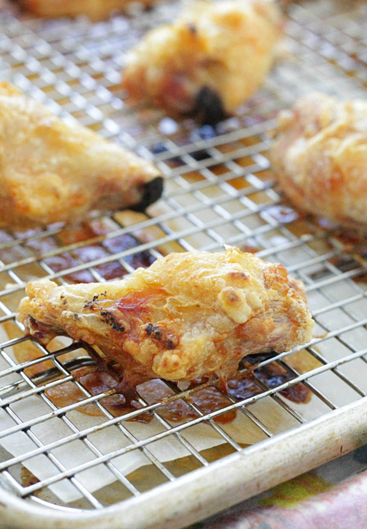 crispy baked chicken wings on sheet pan lined with baking rack showing how crisp the wings are after just being baked