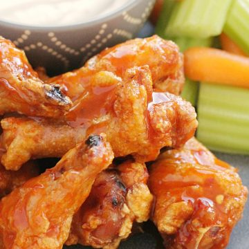 crispy baked chicken wings on a grey plate with celery carrots and blue cheese dressing