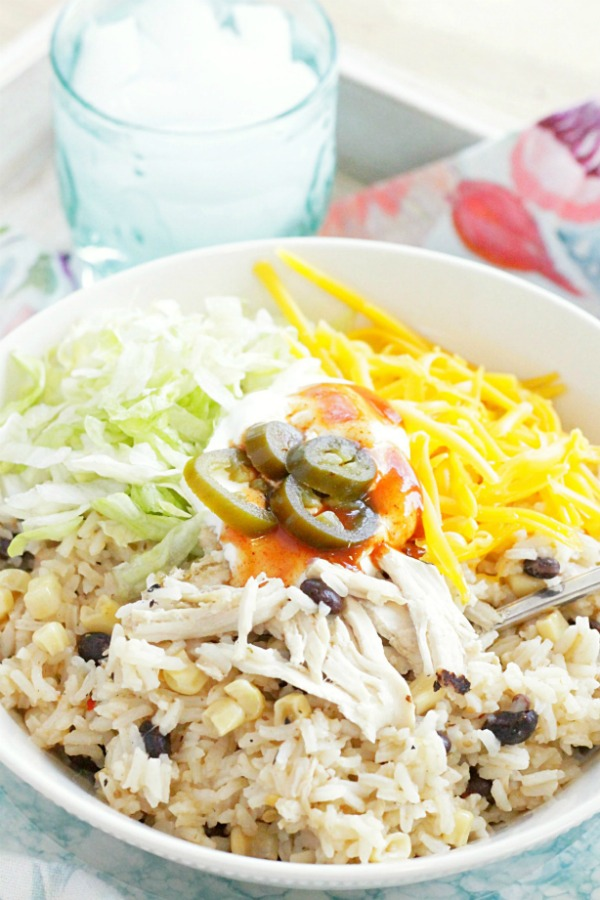 loaded chicken burrito bowl with glass of water