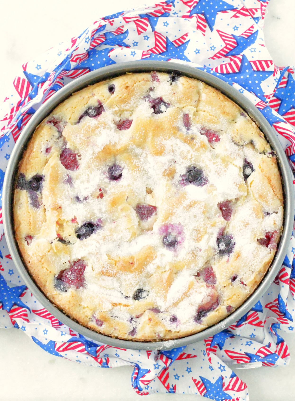 top view of whole red white and blue berry cake in the pan