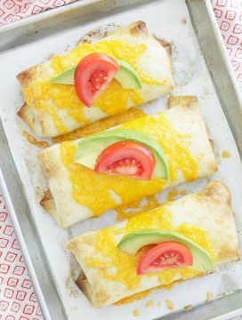 oven fried chimichangas overhead baked on sheet pan and topped with fresh tomato and avocado