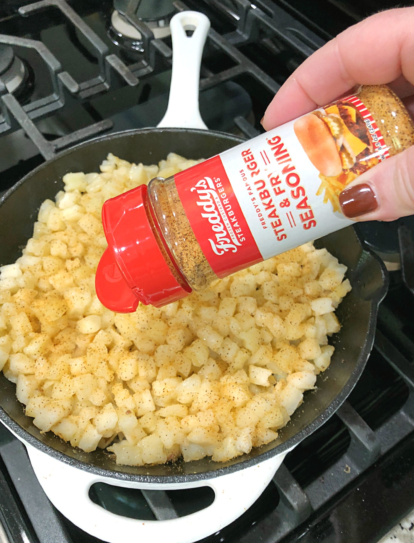 hamburger hashbrown skillet - Freddy's seasoning being shaken into skillet with cubed hashbrown potatoes