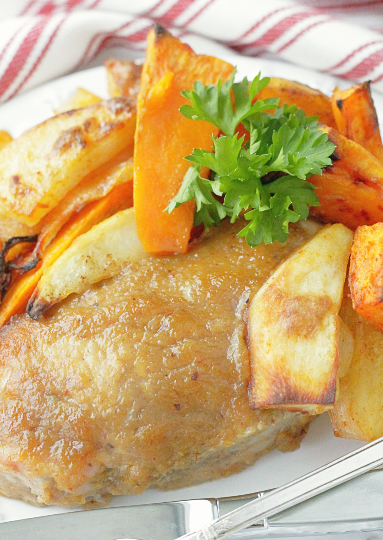 close up of applesauce baked pork chop on a plate with roasted potatoes