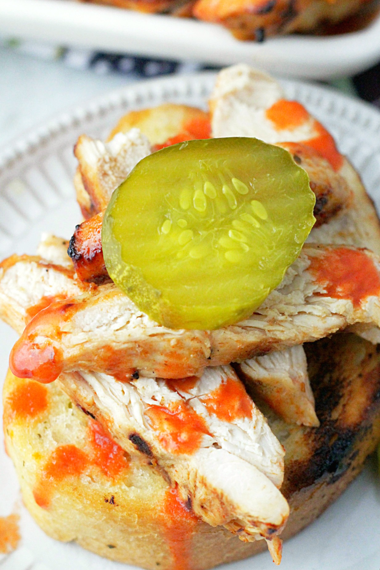 nashville hot grilled chicken on garlic bread topped with a dill pickle slice