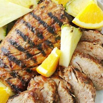 al pastor grilled pork tenderloin on plate with fresh pineapple and orange slices