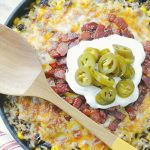 one skillet cowboy rice topped with bacon, sour cream and pickled jalapeños