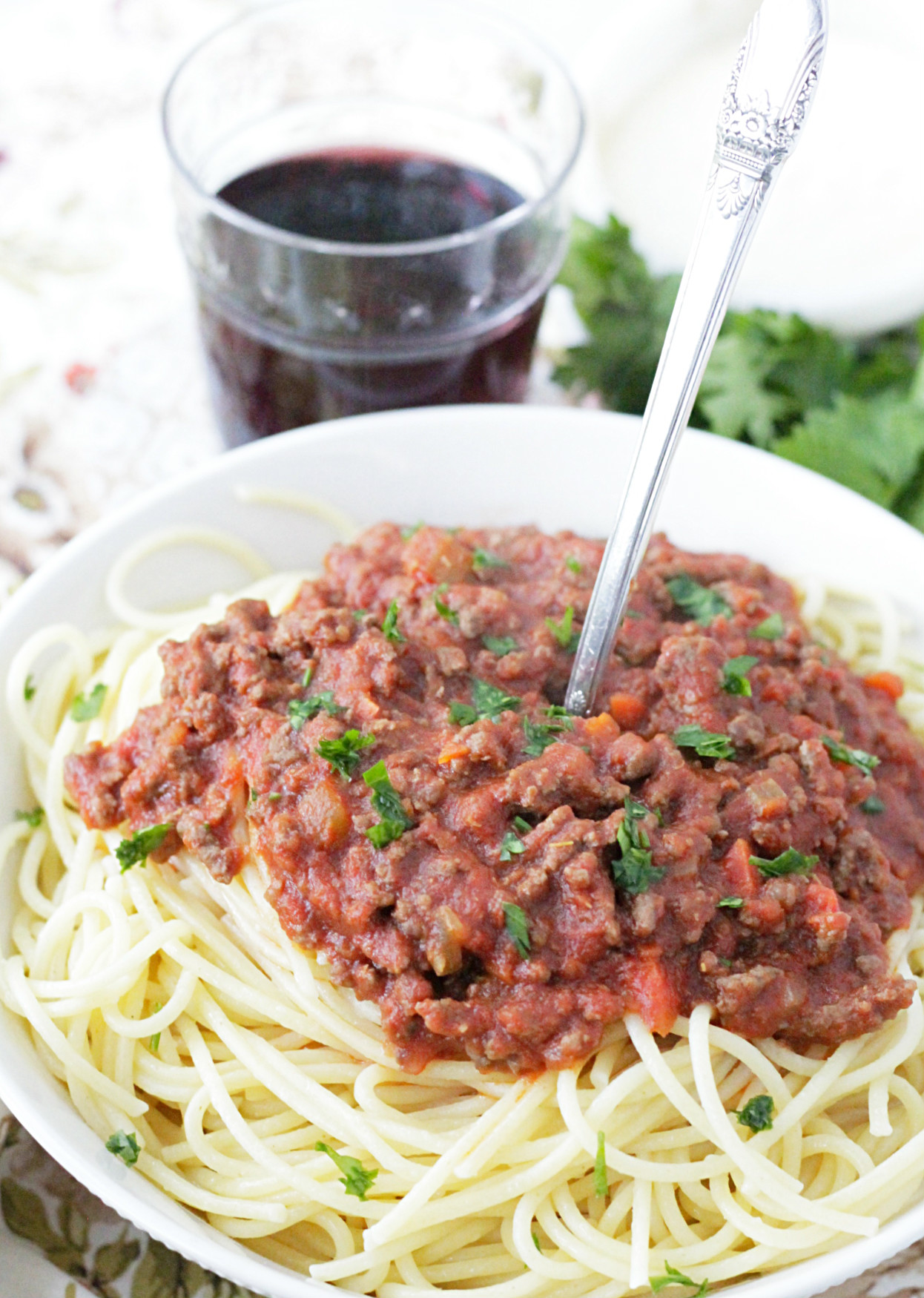 instant pot beef bolognese pasta sauce in a bowl with a glass of red wine on the side