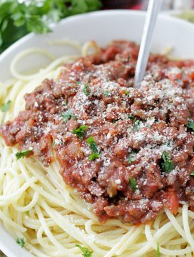 instant pot beef bolognese pasta sauce on spaghetti and topped with parmesan cheese
