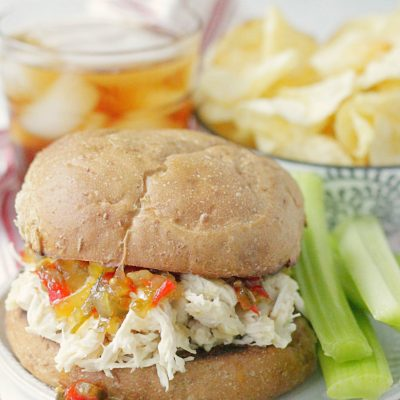 shredded chicken sandwich on plate with celery
