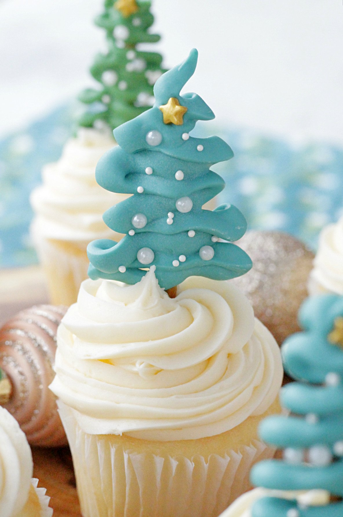 single christmas tree cupcake topper on top of cupcake on wooden platter