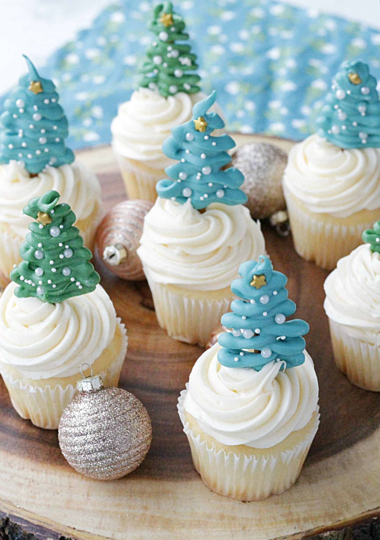 wooden platter of cupcakes topped with christmas tree cupcake toppers