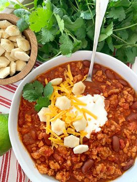 overhead view of turkey chili topped with sour cream, oyster crackers and shredded cheese
