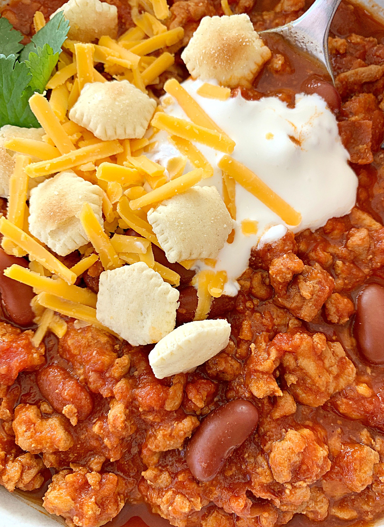 close up view of crockpot turkey chili topped with sour cream, oyster crackers and shredded cheese