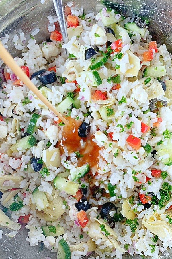 dressing being poured onto greek rice salad