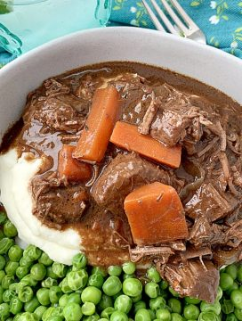 guinness beef stew in bowl with mashed potatoes and peas