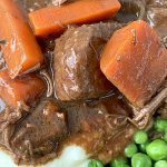 close up of guinness beef stew with carrots and peas