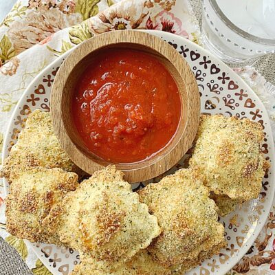 air fryer toasted ravioli on plate with bowl of pizza sauce for dipping