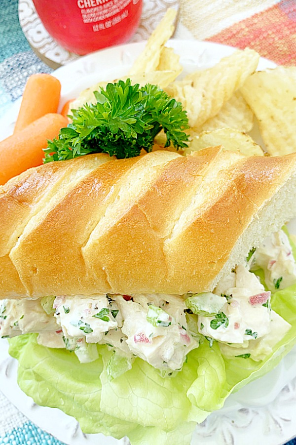 chicken salad sandwich on a plate with chips and carrots