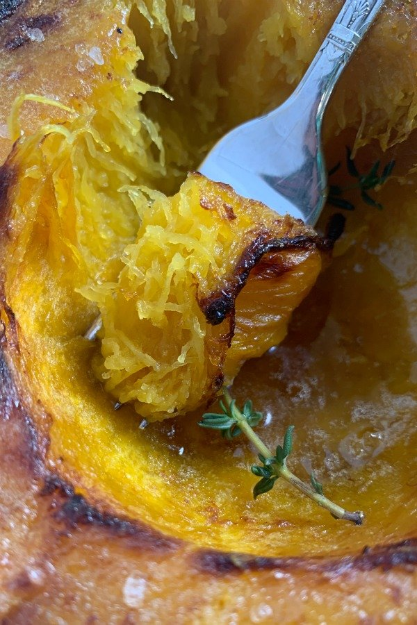 taking a bite of air fryer acorn squash