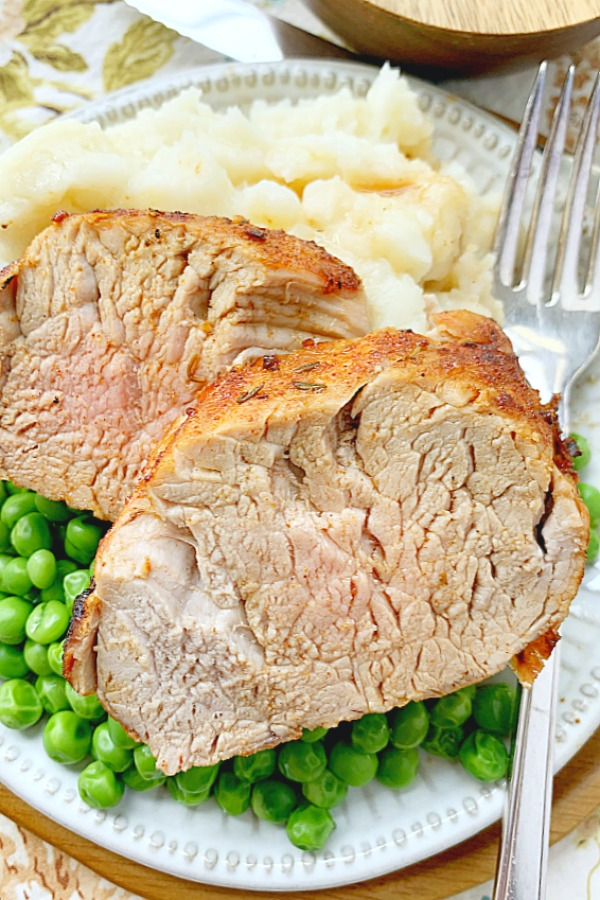pork tenderloin sliced on a plate with potatoes and peas