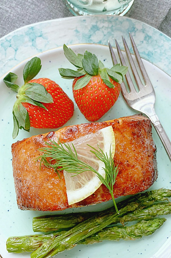 air fryer salmon on plate with asparagus and strawberries